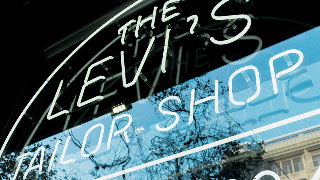 """The window of a Levi's tailor shop with an electric sign saying, """"The Levi's Tailor Shop"""""""