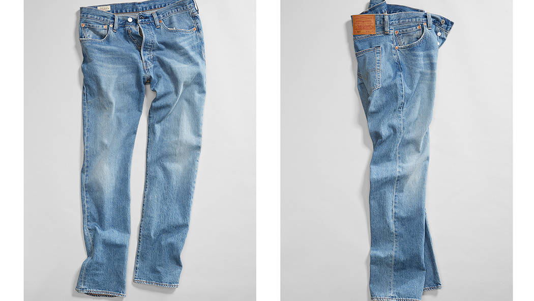A pair of jeans spread out on the ground, two different angles of the jeans are shown.