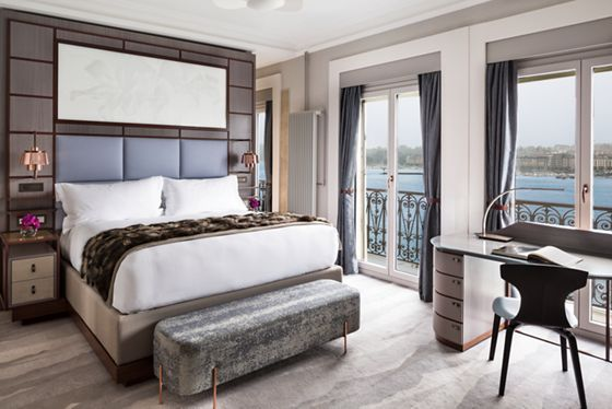 A queen bed and desk with a room with glass doors leading to a lake-view balcony