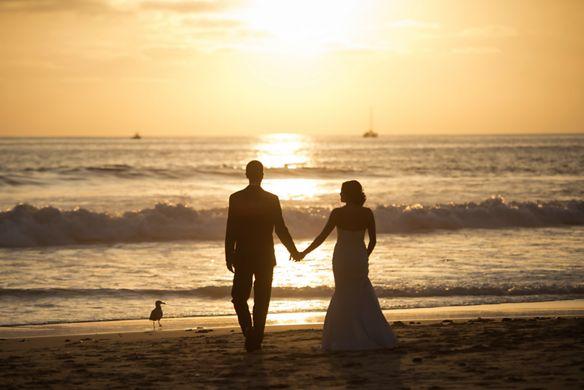 A wedding couple holding hands walks toward the sea as the sun sets