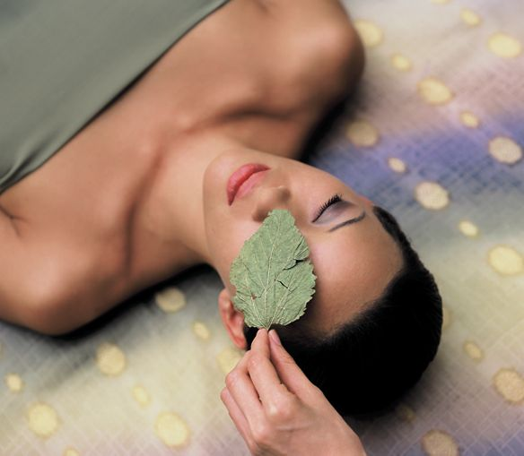 A hand places a leaf over the eye of a woman lying on her back with her eyes closed