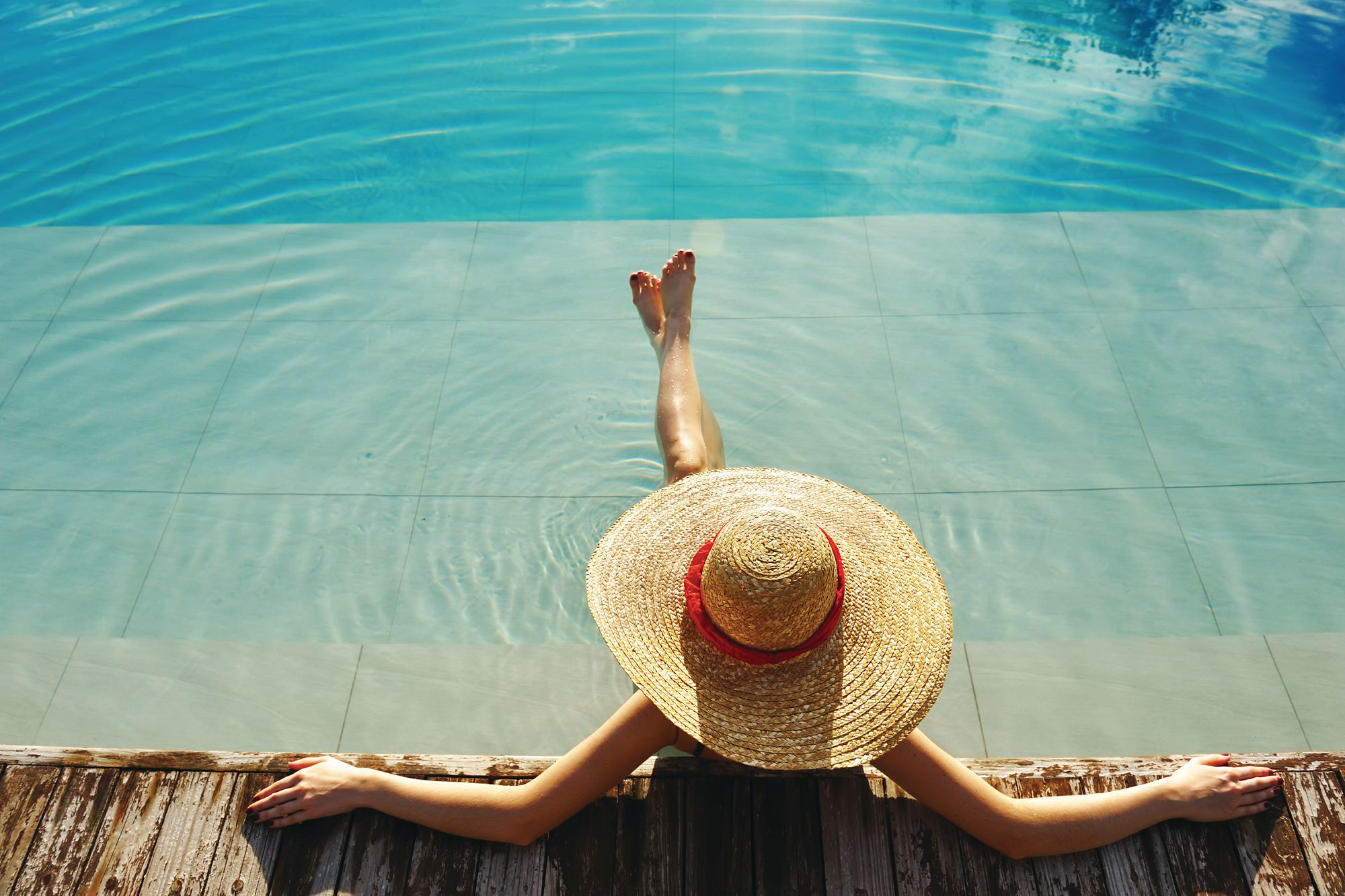 Woman wearing a straw hat sunbathes in a clear, outdoor pool