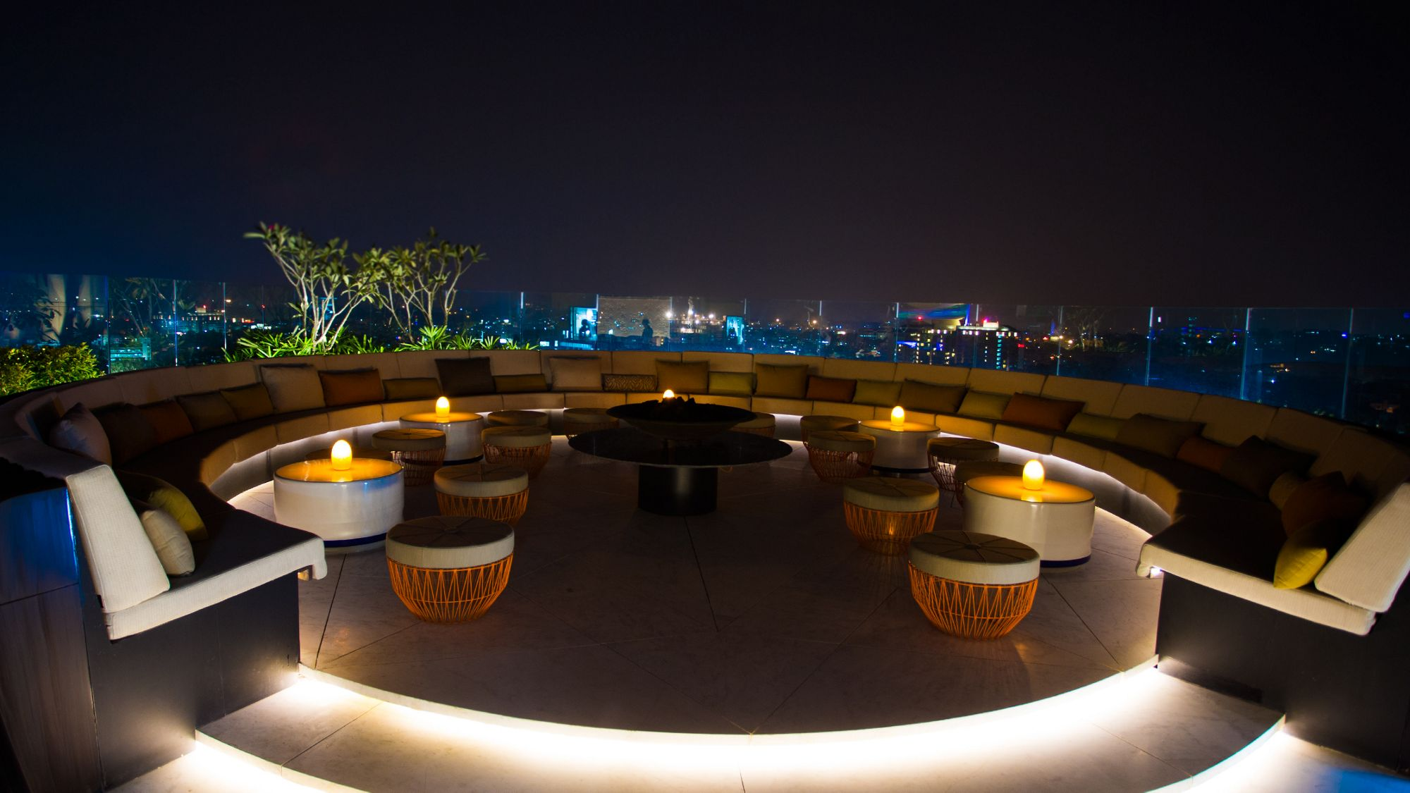 Circular rooftop bar with banquette seating, small round coffee tables and impressive skyline city views at night