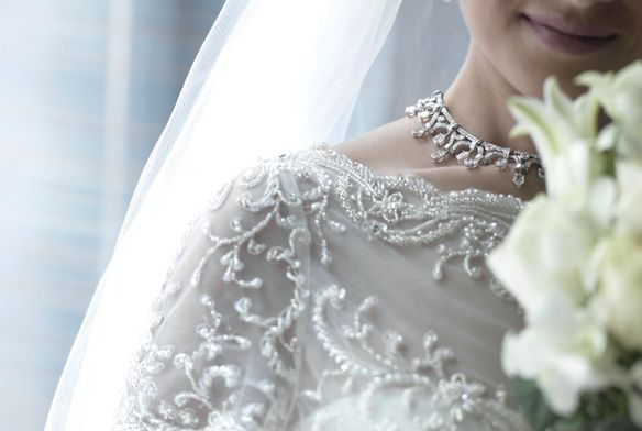 The beaded white dress and collar necklace of a smiling bride with white flowers in the foreground and a veil behind her