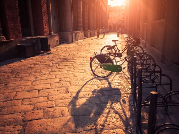 Bicycles parked on sunny cobbled street