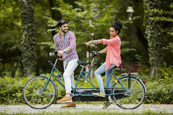 A couple rides a tandem bike