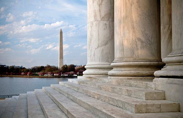 View across marble stairs toward a tall obelisk in the distance
