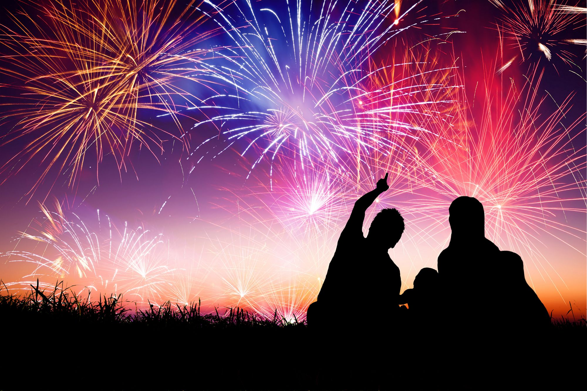 Two people look up at a sky of fireworks