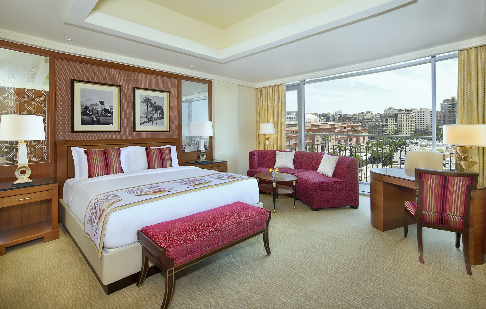 Guest room with a king-size bed, plush red furnishings, wood accents and floor-to-ceiling views of the city