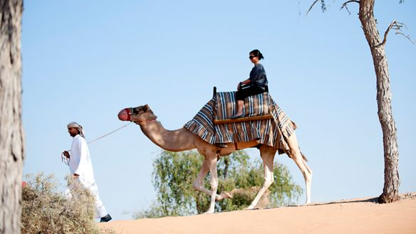 A woman atop a camel being led by a man in traditional Bedouin dress