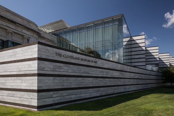 A sunny, lawn view of the modern exterior of the Cleveland Museum of Art.