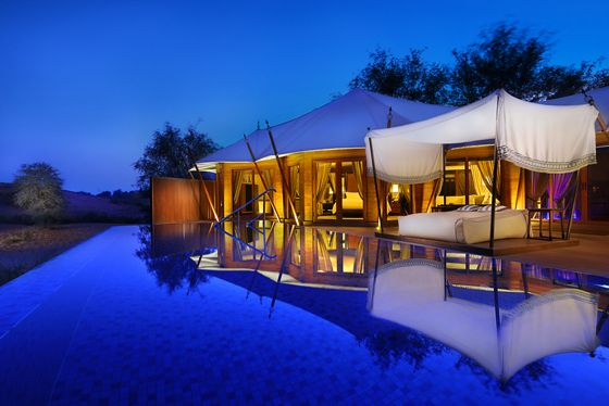A tented, house-like structure and an outdoor bed with a canopy overlook a pool in the evening