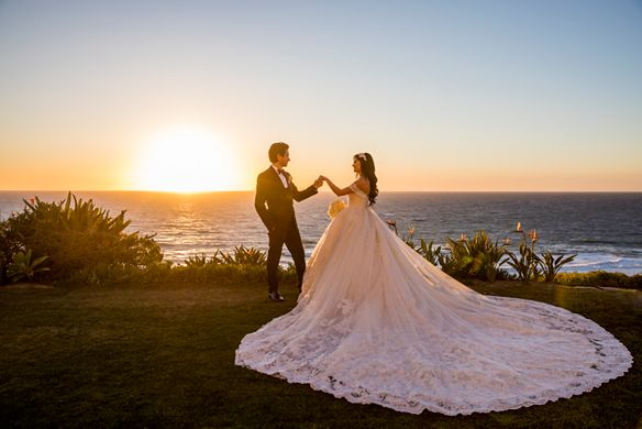 Bride and groom overlooking the ocean at sunset