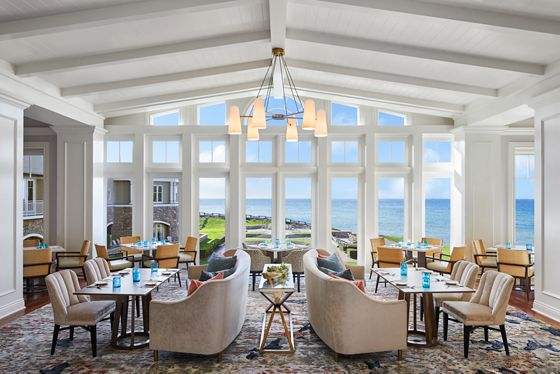 Airy space with dining tables and an entire wall of windows overlooking the ocean
