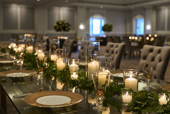 A long dining table with formal centerpieces and settings