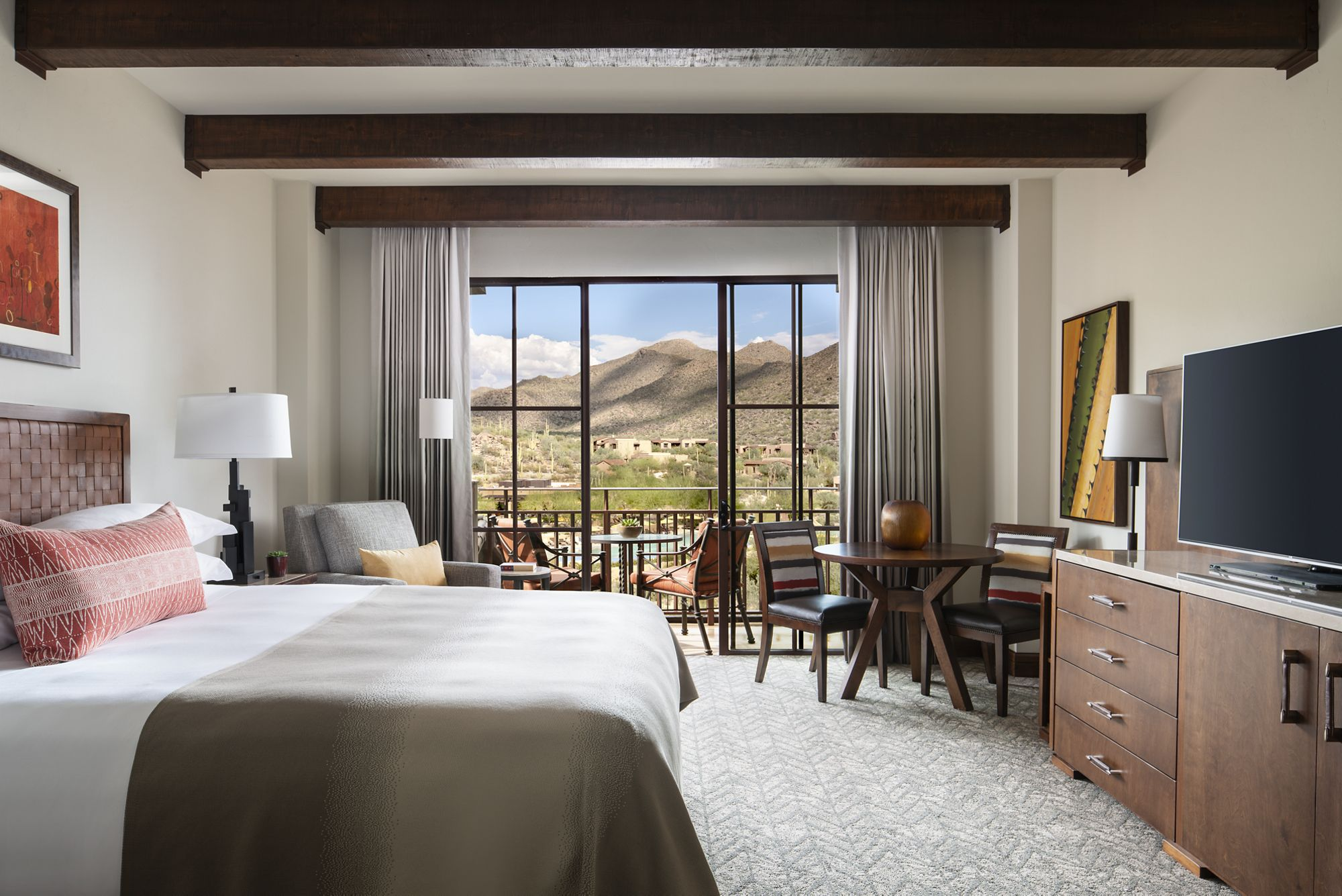 Hotel room with a wooden table a bed and a balcony overlooking the desert foothills.