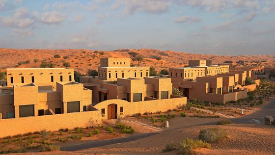 Exterior view of sand-colored, multi-level villas enclosed by privacy walls and surrounded by the desert and sky