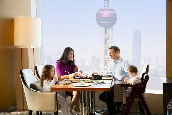 Two parents and their two small children eat breakfast next to a large window with views of the Oriental Pearl Tower