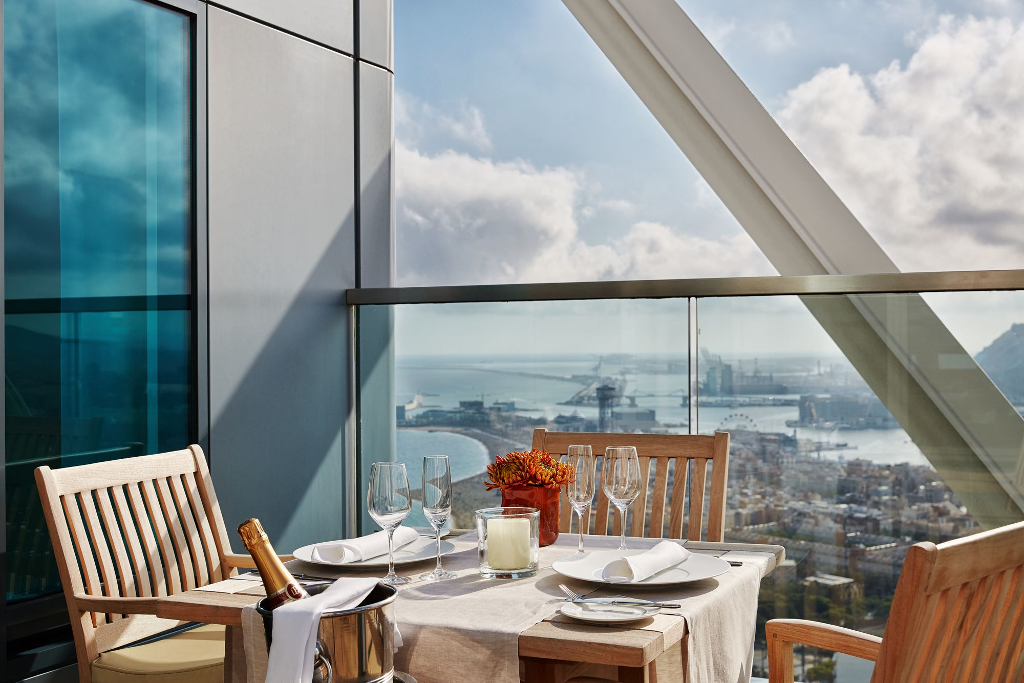 A dining table on a terrace overlooking the city and sea