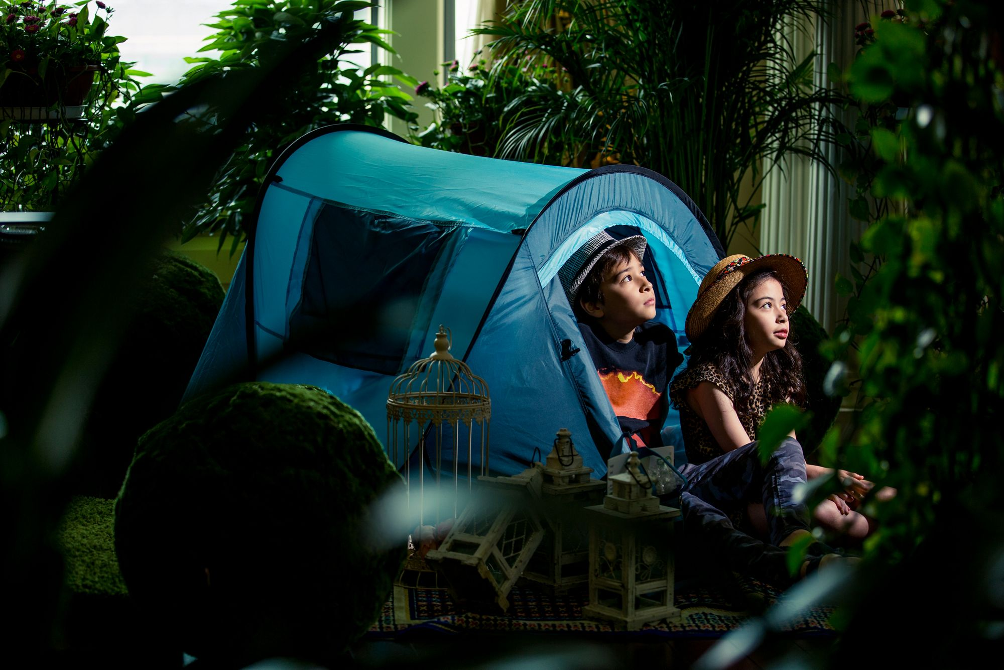 Two kids peek out of an indoor tent surrounded by plants