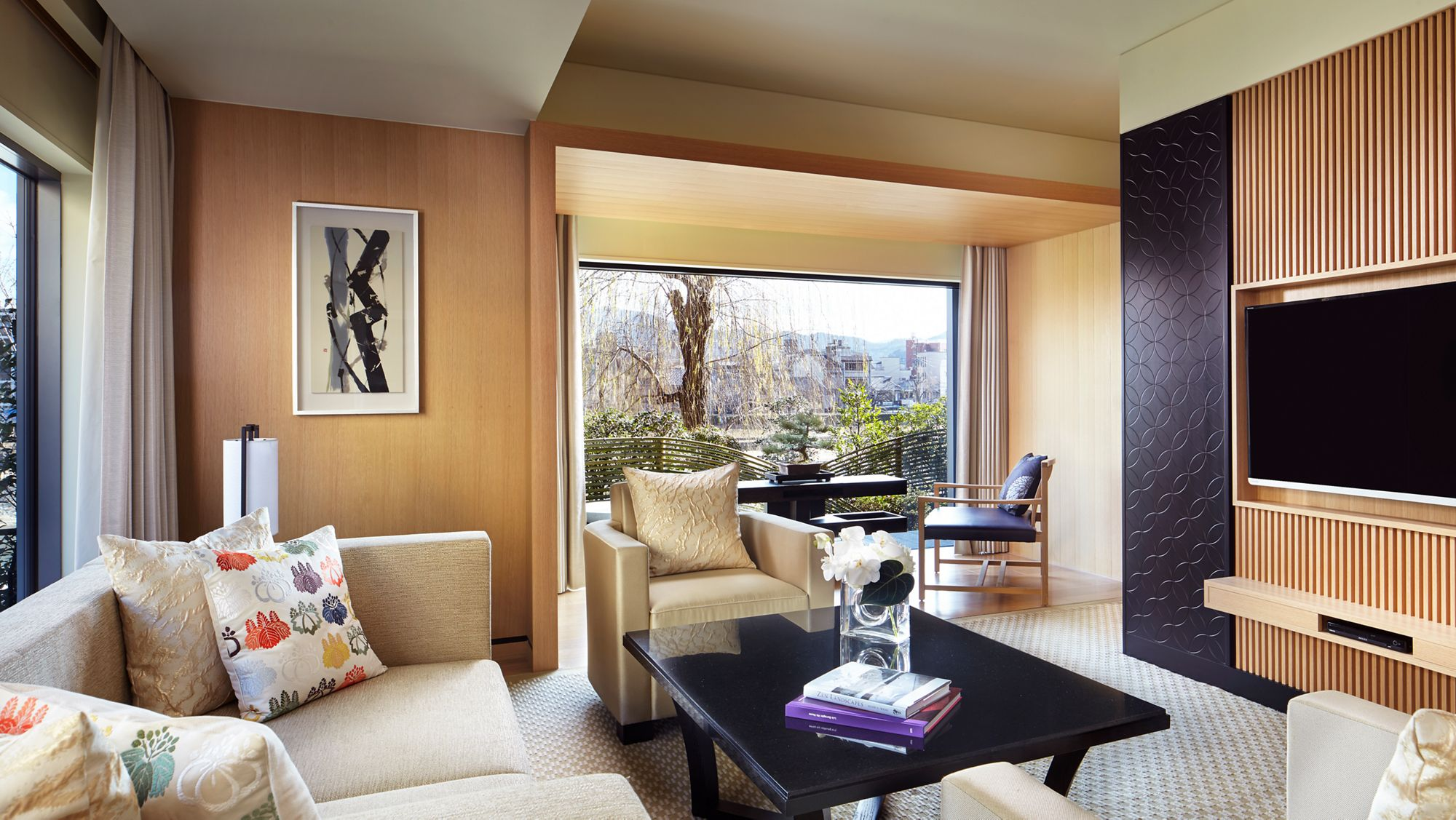 Room with a sofa, armchairs, coffee table, wall-mounted flat-screen TV and a floor-to-ceiling window overlooking a garden