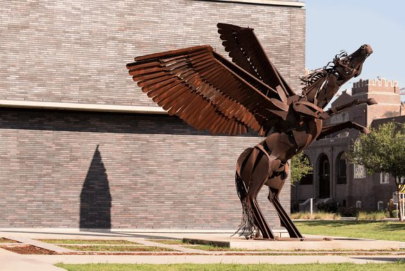 A metallic sculpture of a horse with wings on its hind legs