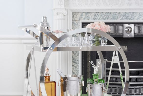 A cocktail shaker, a set of crosshatch highball glasses, fresh pink roses and a pristine ice bucket decorate the Asprey Drink Trolley.