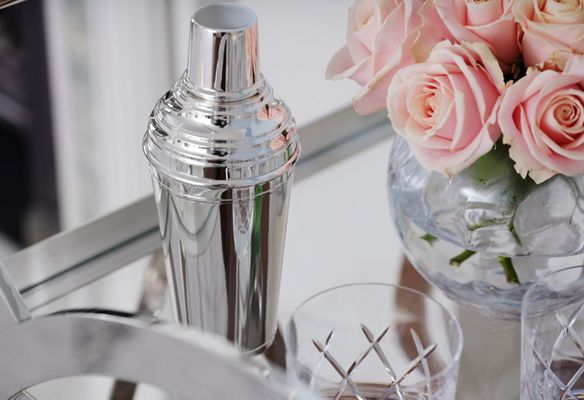 A close-up view of the Asprey Drink Trolley's specialty cocktail shaker, crosshatch lowball glasses and pink roses.