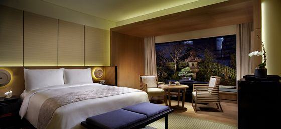 Room with a king bed, table for two and a floor-to-ceiling window overlooking a garden at night