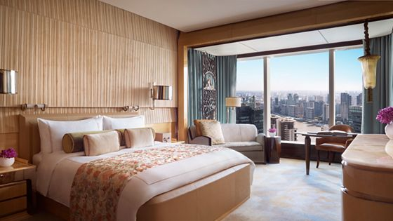 Guest room with a king-size bed, natural wood wall treatments and a sitting area with skyline views