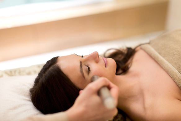 Woman in a tan towel reclines with her eyes closed as an aesthetician treats her face