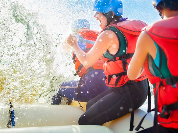 A river-rafting group laughs while being splashed