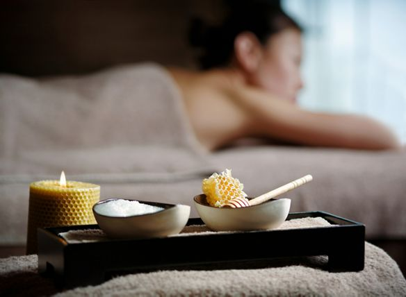 Two bowls bearing ingredients like milk and honeycomb rest on a tray while a woman reclines in the background