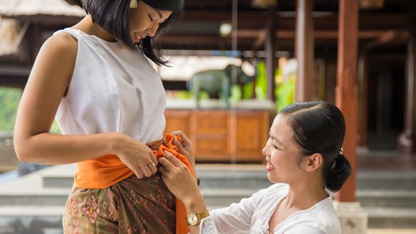 Smiling woman belts an orange scarf around the waist of another woman