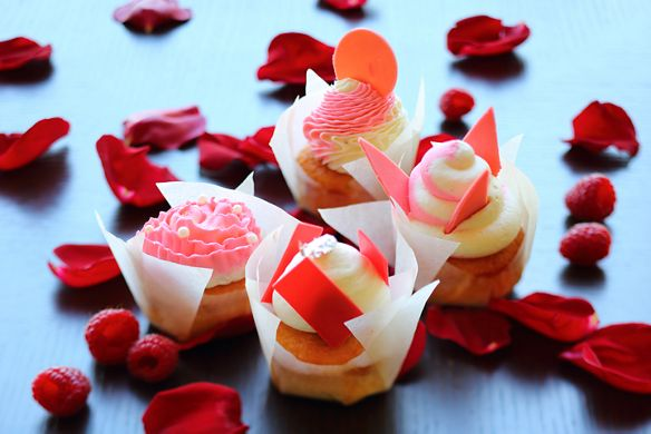 Four vanilla cupcakes, each with an original pink-and-white frosting design, surrounded by raspberries and red rose petals