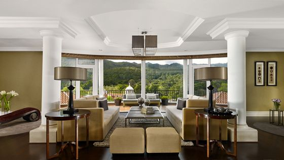 A large living room with multiple seating areas and a semi-circular window niche overlooking green hills