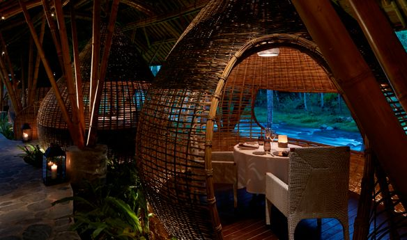 Teardrop-shaped cocoon fashioned from bamboo with a table set for two inside