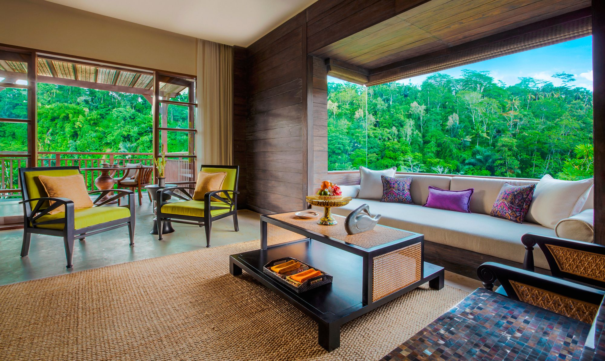 Suite living room with an open terrace, Balinese furniture and a daybed tucked into an expansive windowed alcove
