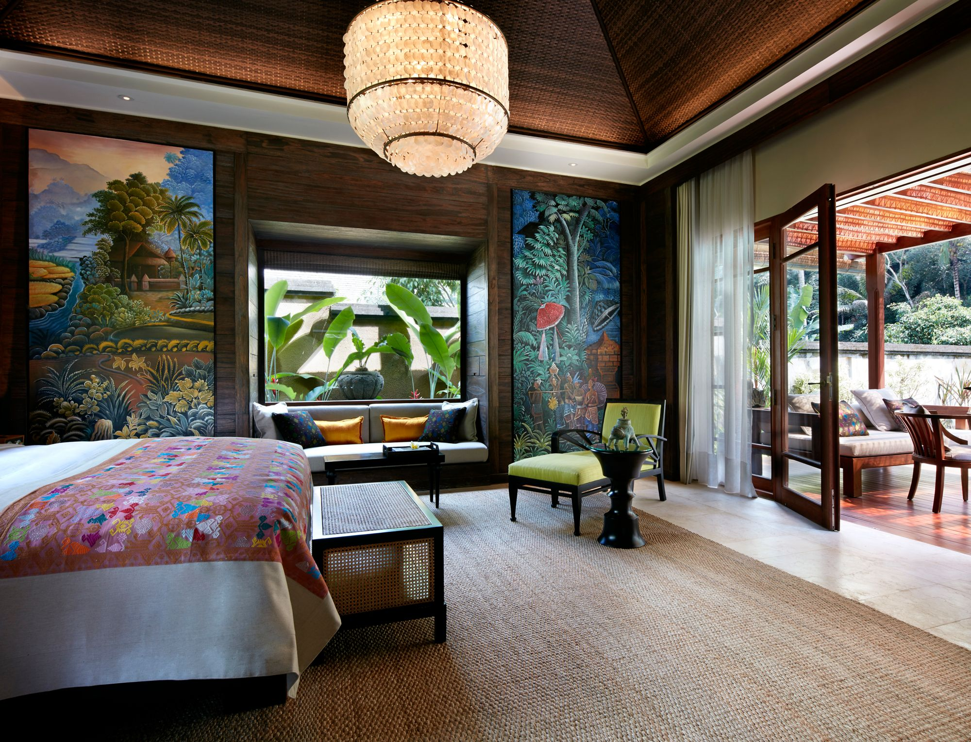 Bedroom featuring floor-to-ceiling Balinese artwork as well as a king bed facing glass doors that open onto the terrace