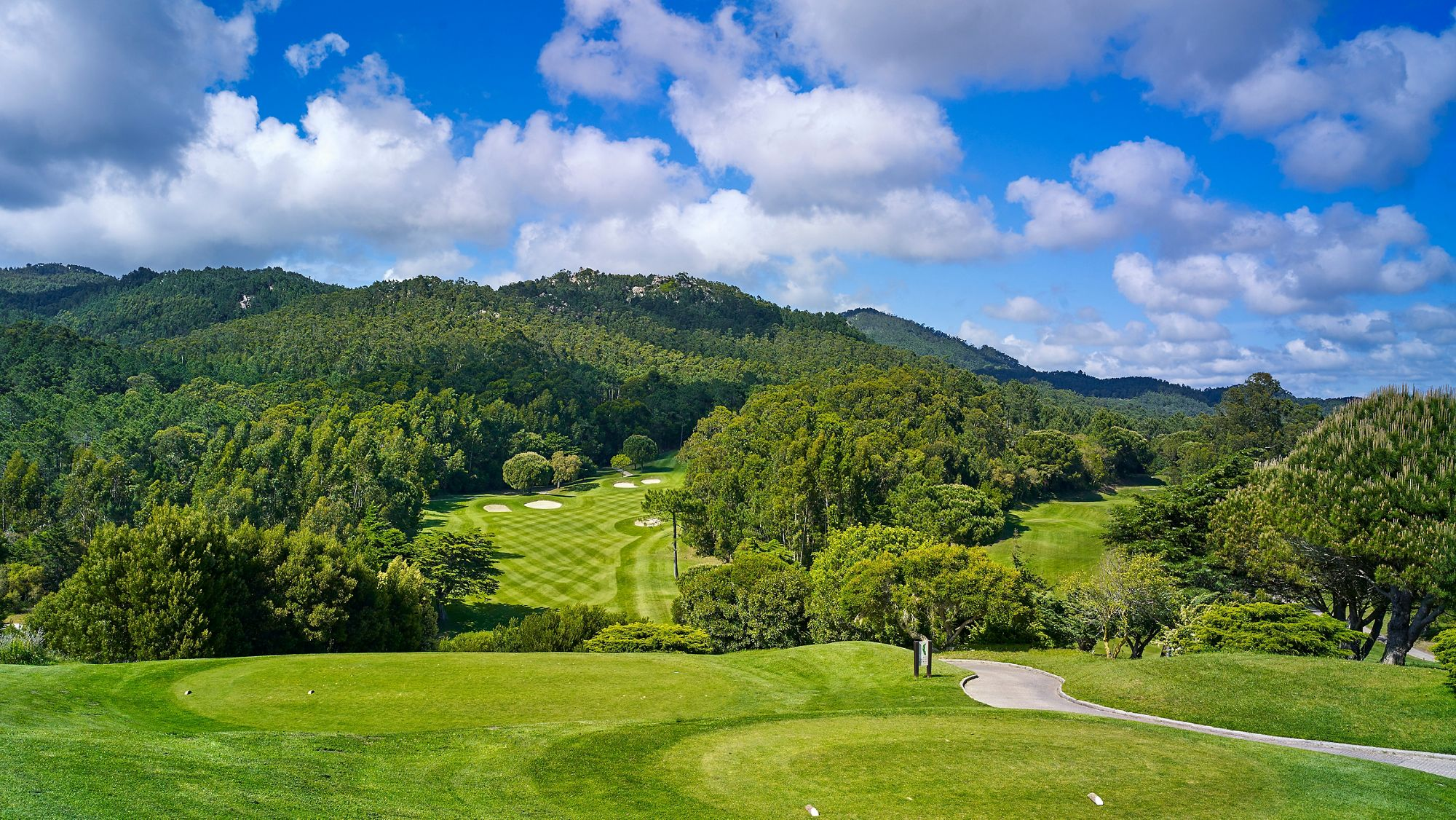 A large golf course overlooked by rolling hills and trees