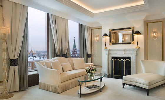 A living room with a sofa, large chaise, fireplace and windows overlooking the city