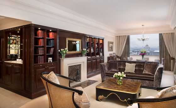 An open living space with seating and dining areas, a fireplace and wood bookshelves