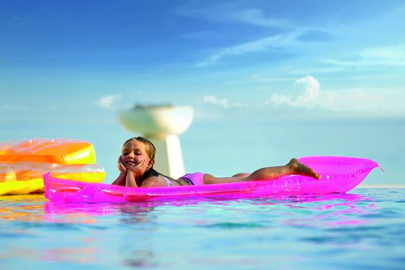 Little girl smiles as she floats on an inflatable pink raft in the crystalline pool