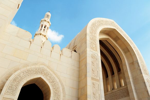 Upward view of a grand mosque built in white stone with a minaret and blue skies in the background