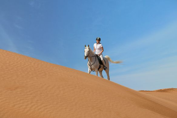 Woman rides a white horse on a sand dune against a bright blue sky