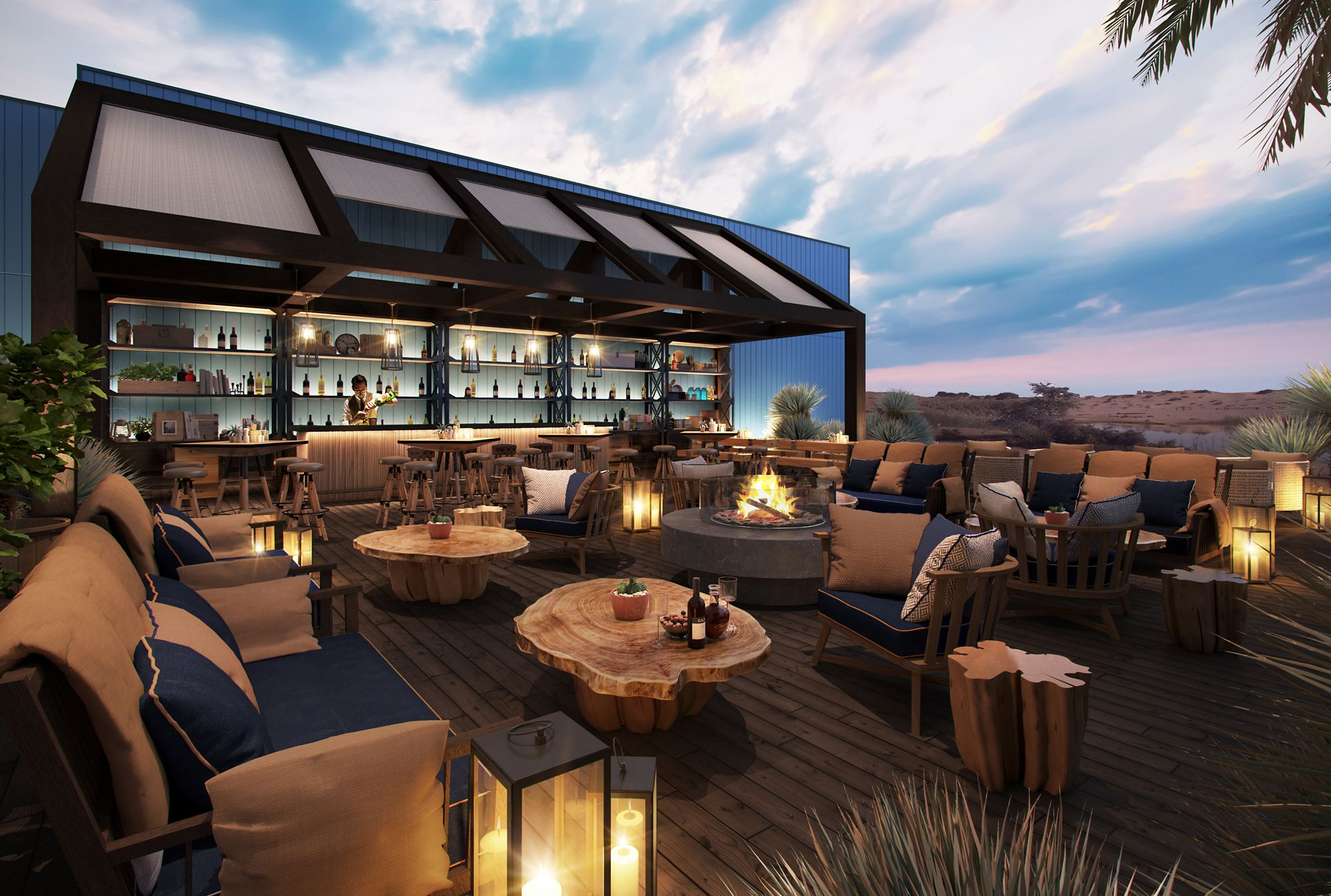 Outdoor seating with black-and-tan couches and chairs and wood-slab tables as well as a covered bar area