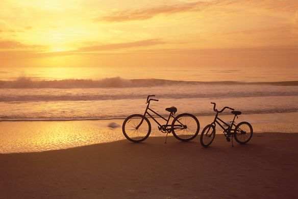 Two bikes on the beach at sunset