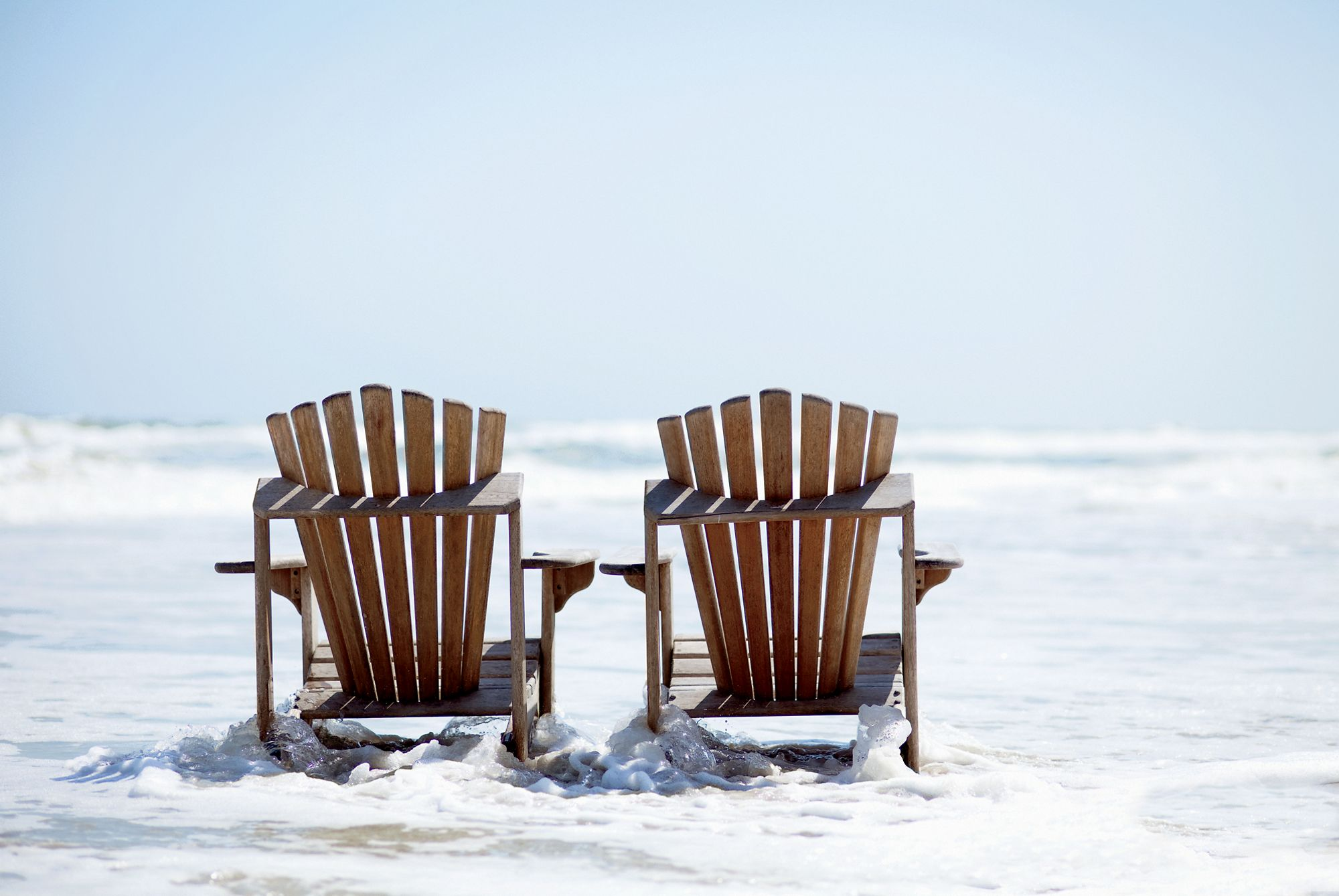 Two Adirondack chairs at the edge of the ocean