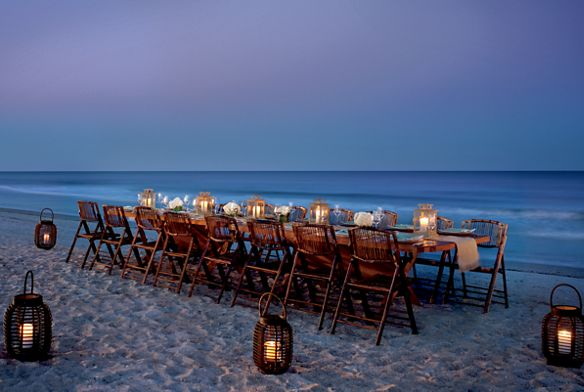 A long candle-lit dining table on the beach