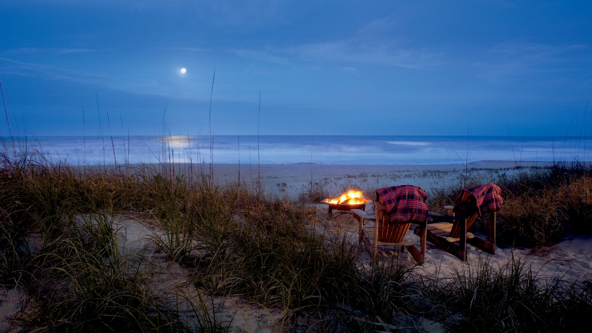 Two Adirondack chairs sit in front of a fire pit on the beach with a full moon hovering above the ocean